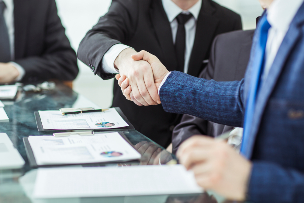 a borrower shakes hands with a lender when borrowing a business loan