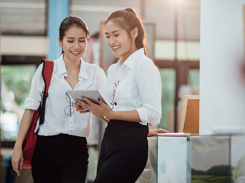 two young, happy women searching best study loan to cover higher education costs