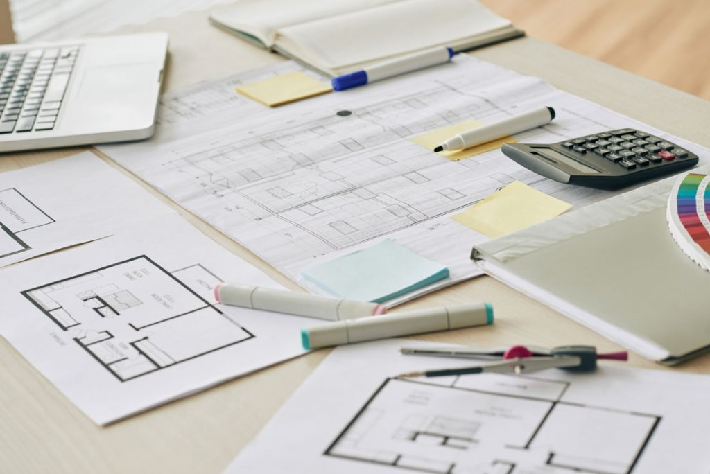 finding the hidden renovation costs using calculator, pens, layouts to factor in the budget
