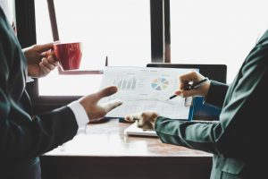 two professionals discussing company growth after borrowing a business loan from moneylender