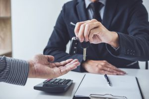 A customer receives the keys to his car after successfully taking out a Grab loan